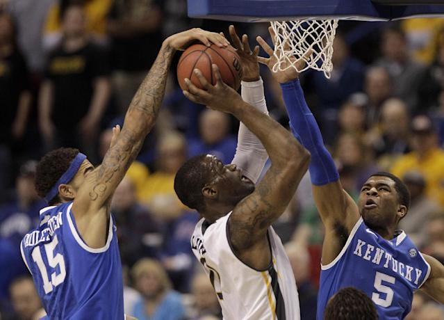 Wichita State's Chadrack Lufile (0) shoots under pressure from Kentucky's Willie Cauley-Stein (15) and Andrew Harrison (5) during the first half of a third-round game at the NCAA college basketball tournament Sunday, March 23, 2014, in St. Louis. (AP Photo/Charlie Riedel)