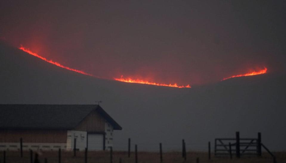 Flames rise from mountain ridges.