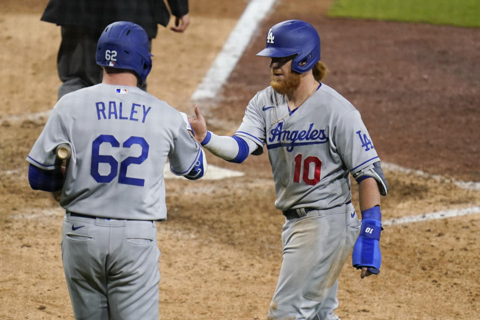 Los Angeles Dodgers' Justin Turner (10) reacts with teammate Luke Raley (62) after scoring off a single by Raley during the twelfth inning of a baseball game against the San Diego Padres, Friday, April 16, 2021, in San Diego. (AP Photo/Gregory Bull)