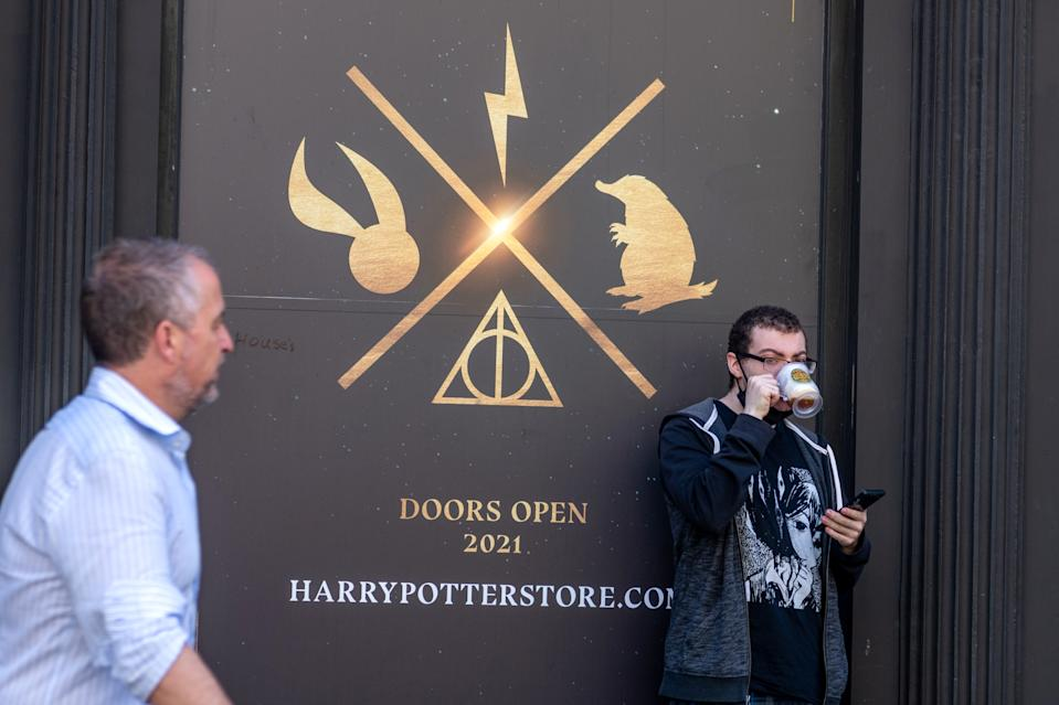 NEW YORK, NEW YORK - MAY 27: A person drinks a 'butterbeer' outside the Harry Potter store in Flatiron on May 27, 2021 in New York City. The 'Harry Potter Wizarding World' store, which includes an immersive retail experience, will open on June 3rd. On May 19, 2021 all pandemic restrictions, including mask mandates, social distancing guidelines, venue capacities and restaurant curfews were lifted by New York Governor Andrew Cuomo. (Photo by Alexi Rosenfeld/Getty Images)