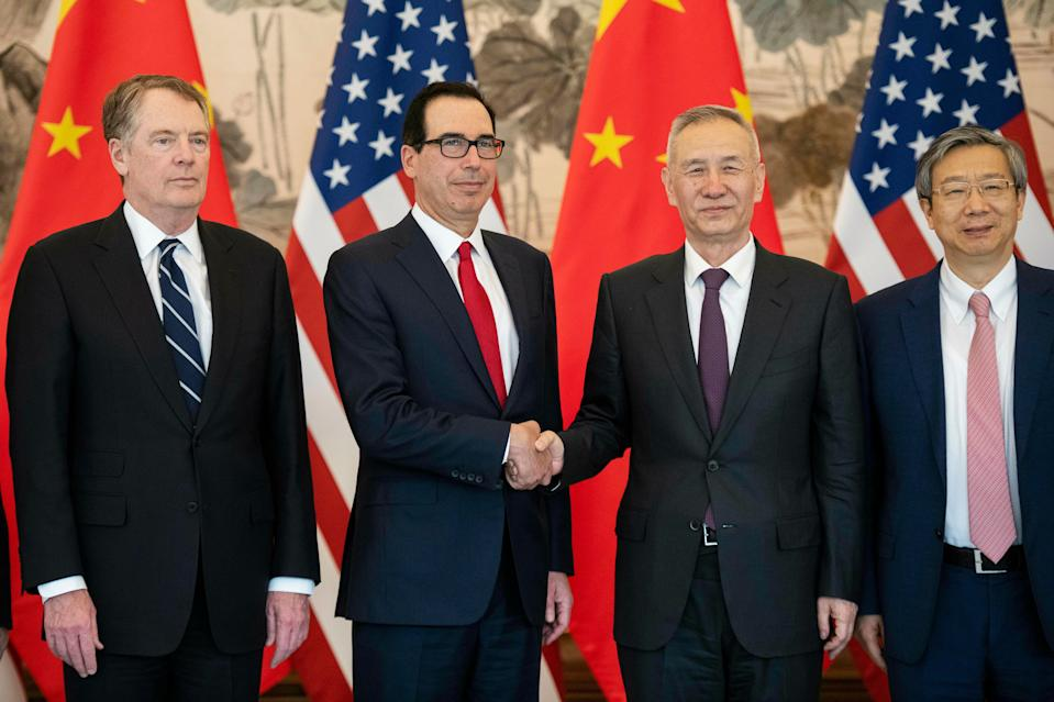 China's Vice Premier Liu He, second right, shakes hands with U.S. Treasury Secretary Steven Mnuchin, second left, as Yi Gang, right, governor of the People's Bank of China (PBC) and U.S. Trade Representative Robert Lighthizer pose for a group photo at Diaoyutai State Guesthouse in Beijing Friday, March 29, 2019. (Nicolas Asfouri/Pool Photo via AP)