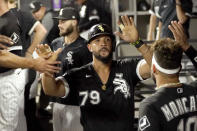 Chicago White Sox's Jose Abreu is greeted in the dugout after he scored on a bases loaded walk by Pittsburgh Pirates relief pitcher Chasen Shreve during the sixth inning of a baseball game Tuesday, Aug. 31, 2021, in Chicago. (AP Photo/Charles Rex Arbogast)
