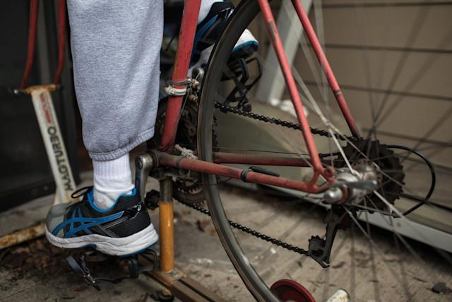 Yarling exercises on his old triathlon bicycle, which he attached to a stationary bike stand on the patio outside his apartment.