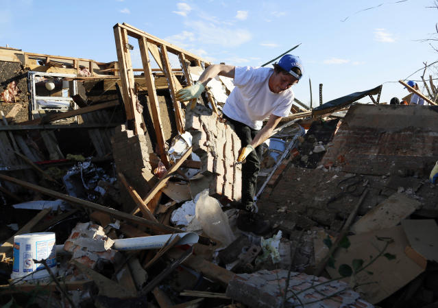 Josh Sallee throws a piece of a brick wall from a tornado-destroyed home on Heather Lane in Moore, Oklahoma May 21, 2013. Rescuers went building to building in search of victims and thousands of survivors were homeless on Tuesday after a massive tornado tore through the Oklahoma City suburb of Moore, wiping out whole blocks of homes and killing at least 24 people. REUTERS/Rick Wilking (UNITED STATES - Tags: DISASTER ENVIRONMENT) - RTXZVR2