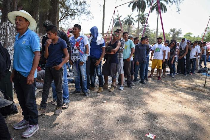 """Central Americans, part of a 'caravan' called """"Migrant Viacrucis""""- wait in line to get a meal in Matias Romero, Oaxaca state, Mexico on April 2, 2018 (AFP Photo/VICTORIA RAZO)"""