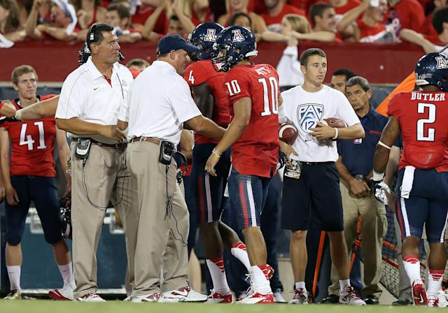 """<a class=""""link rapid-noclick-resp"""" href=""""/ncaab/players/127330/"""" data-ylk=""""slk:Matt Scott"""">Matt Scott</a> and Rich Rodriguez chat on the sideline during an Arizona football game in September 2012. (Getty Images)"""