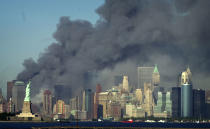 <p>Thick smoke billows into the sky from the area behind the Statue of Liberty, lower left, where the World Trade Center was. (AP)</p>