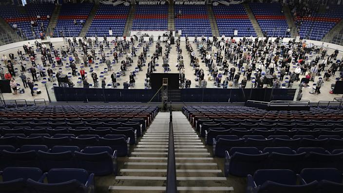 Members of the New Hampshire House of Representatives stand at the start of their session in Durham on Thursday, June 11, 2020, at the Whittemore Center at the University of New Hampshire. The Legislature, which suspended its work in March because of the COVID-19 virus outbreak, gathered at the arena for the first House session held outside the Statehouse since the Civil War.