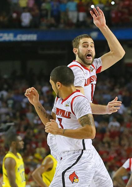 Louisville guard Peyton Siva (left) and forward Luke Hancock (right) start the celebration as time runs out defeating Michigan to win the NCAA Division I National Championship on Monday, April 8, 2013, in Atlanta. Louisville beat Michigan 82-76 for NCAA title. (AP Photo/Atlanta Journal Constitution, Curtis Compton)