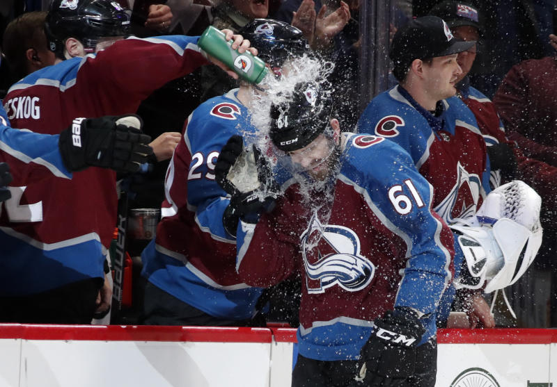 Teammates douse Colorado Avalanche right wing Martin Kaut as he pases the teambox after scoring his first professional goal against the Buffalo Sabres in the second period of an NHL hockey game Wednesday, Feb. 26, 2020, in Denver. (AP Photo/David Zalubowski)