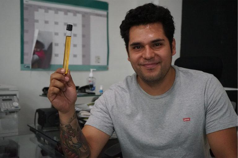 Moises Flores with a test tube sample of his biodiesel