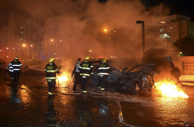 Israeli firefighters work to put out fire on burning cars in an apartment building parking lot after it was hit by what Israeli police say was a rocket fired by Palestinians from the Gaza Strip, in Ashdod July 10, 2014. At least 77 Palestinians, most of them civilians, have been killed in Israel's Gaza offensive, Palestinian officials said on Thursday, and militants kept up rocket attacks on Tel Aviv, Jerusalem and other cities in warfare showing no signs of ending soon. REUTERS/ Avi Rokach (ISRAEL - Tags: POLITICS CIVIL UNREST) ISRAEL OUT. NO COMMERCIAL OR EDITORIAL SALES IN ISRAEL