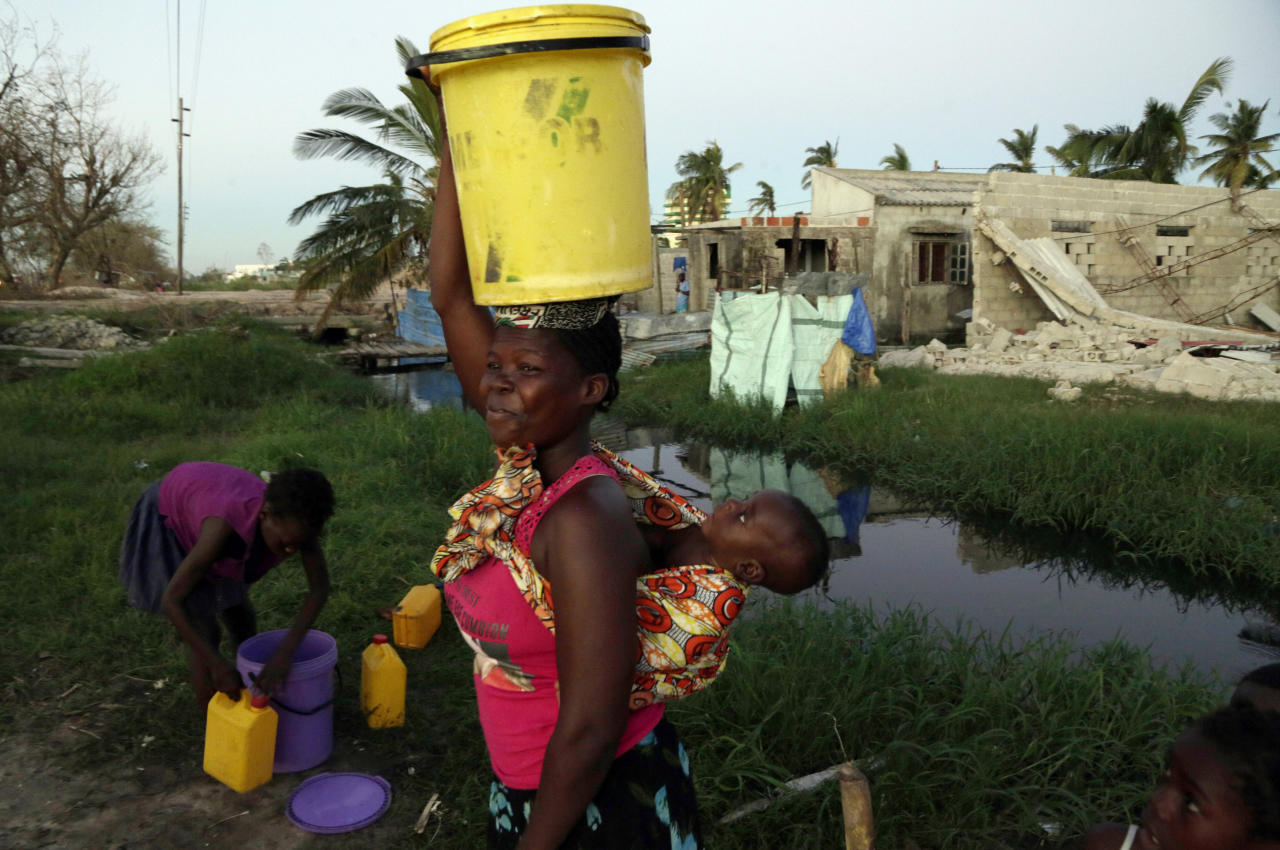A woman carrying water and a baby on her back after collecting water in Beira, Mozambique, Monday, March 25, March 24, 2019. (AP Photo/Themba Hadebe)