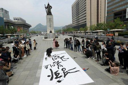 South Korean calligraphist Kang Byung In writes a goodwill message during a pro-unification rally ahead of the upcoming summit between North and South Korea in Seoul, South Korea April 26, 2018. REUTERS/Jorge Silva