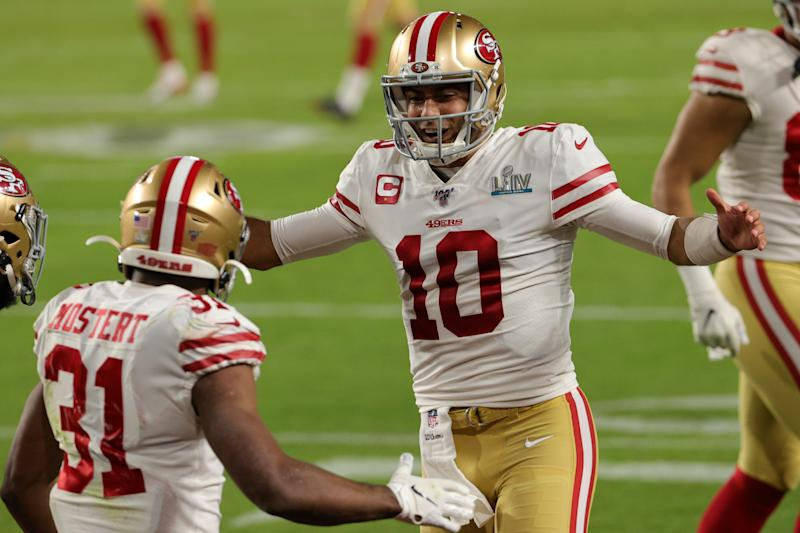 Jimmy Garoppolo, right, soon can celebrate with Raheem Mostert, left, after the running back's contract adjustment. (Photo by Sam Greenwood/Getty Images)