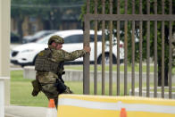 A military policeman closes a gate at JBSA-Lackland Air Force Base, Wednesday, June 9, 2021, in San Antonio. The Air Force was put on lockdown as police and military officials say they searched for two people suspected of shooting into the base from outside. (AP Photo/Eric Gay)