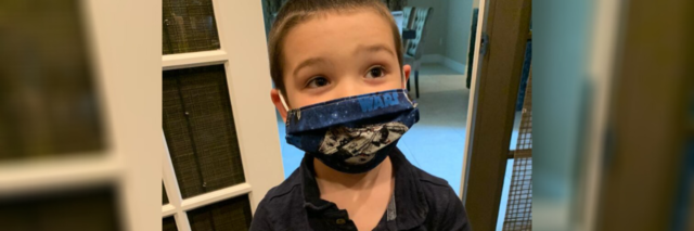 Amy's son on the autism spectrum wearing his Star Wars face mask.