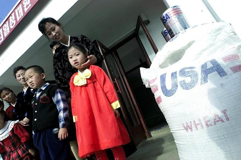 North Korean children stand next to shipment of US wheat, in Pyongyang, on October 23, 2000