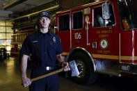 Fire engine probationary firefighter Cole Gomoll of Los Angeles County Fire Department - Station 106 poses for a photo with a flathead ax at his station Friday, Feb. 26, 2021, in Rancho Palos Verdes, Calif, a suburb of Los Angeles. He used the ax to cut away the windshield of a vehicle crashed by golfer Tiger Woods on Tuesday. (AP Photo/Ashley Landis)