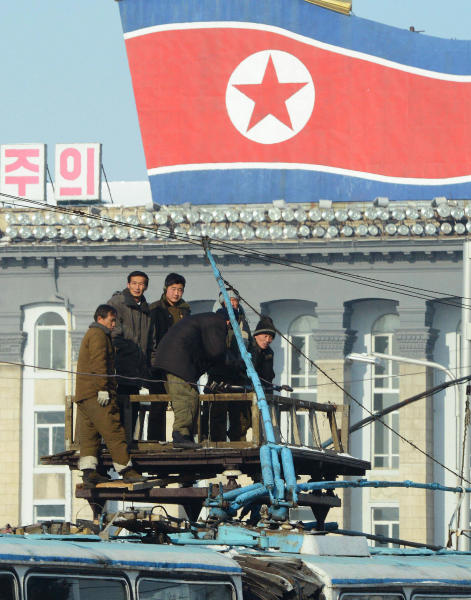 North Korean men work atop a trolleybus in Pyongyang, North Korea Monday, Dec. 10, 2012. North Korea on Monday extended the launch period for a controversial long-range rocket by another week until Dec. 29, citing technical problems. (AP Photo/Kyodo News) JAPAN OUT, MANDATORY CREDIT, NO LICENSING IN CHINA, FRANCE, HONG KONG, JAPAN AND SOUTH KOREA