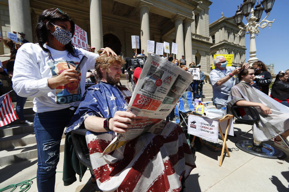 Jody Hebberd, left, gives a free haircut to Reid Scott, as he reads the paper on the steps of the State Capitol as Karl Manke, right, cuts the hair of Parker Shonts during a rally in Lansing, Mich., Wednesday, May 20, 2020. Barbers and hair stylists are protesting the state's stay-at-home orders, a defiant demonstration that reflects how salons have become a symbol for small businesses that are eager to reopen two months after the COVID-19 pandemic began. (AP Photo/Paul Sancya)