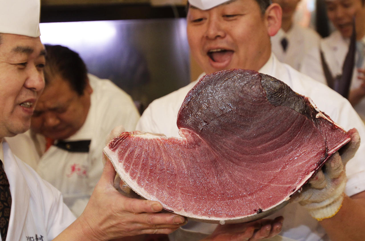 Sushi chefs of Kiyomura Co. hold a slice of a bluefin tuna at their Sushi Zanmai restaurant near Tsukiji fish market in Tokyo Thursday, Jan. 5, 2012. The bluefin tuna caught off northeastern Japan fetched a record 56.49 million yen, or about $736,000, Thursday in the first auction of the year at the fish market. The tuna was caught off Oma in Aomori prefecture and just north of the coast that was battered by the March 11 tsunami. (AP Photo/Shizuo Kambayashi)