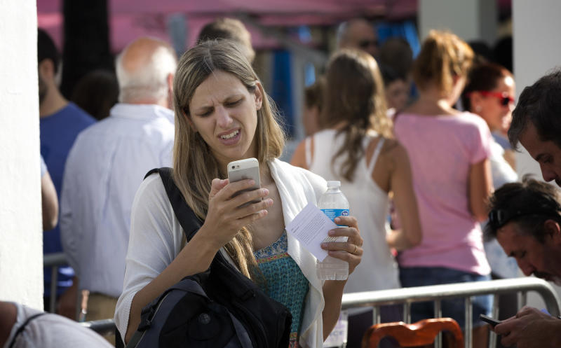 A woman woman stands in line, outside the Apple Store on Lincoln Road in Miami Beach, Fla., Friday, Sept. 20, 2013. Friday is the first time Apple is releasing two different iPhone models at once. (AP Photo/J Pat Carter)