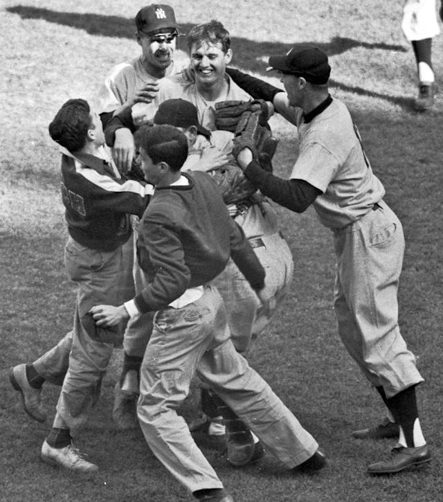 FILE - In this Oct. 10, 1956, file photo, New York Yankees pitcher Johnny Kucks, top center, is mobbed by teammates and fans after striking out Brooklyn Dodgers' Jackie Robinson for the final out to win Game 7 of baseball's World Series at Ebbets Field in New York. Kucks, who pitched a three-hitter for the Yankees in Game 7 of the 1956 World Series, died Thursday, Oct. 31, 2013. He was 81. (AP Photo/File)