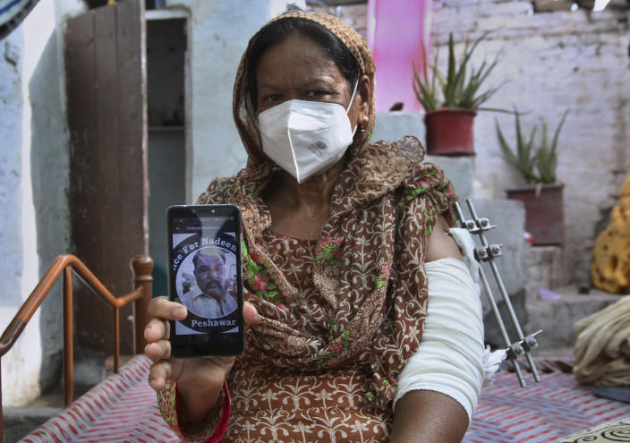 Elizabeth Lal, a Christian woman who was injured and her son-in-law Nadeem Jordon killed by gunmen because he rented in a Muslim neighborhood, shows a picture of Jordon on her mobile during an interview with the Associated Press, in Peshawar, Pakistan, Thursday, July 9, 2020. Analysts and activists say minorities in Pakistan are increasingly vulnerable to Islamic extremists as Prime Minister Imran Khan vacillates between trying to forge a pluralistic nation and his conservative Islamic beliefs. (AP Photo/Muhammad Sajjad)