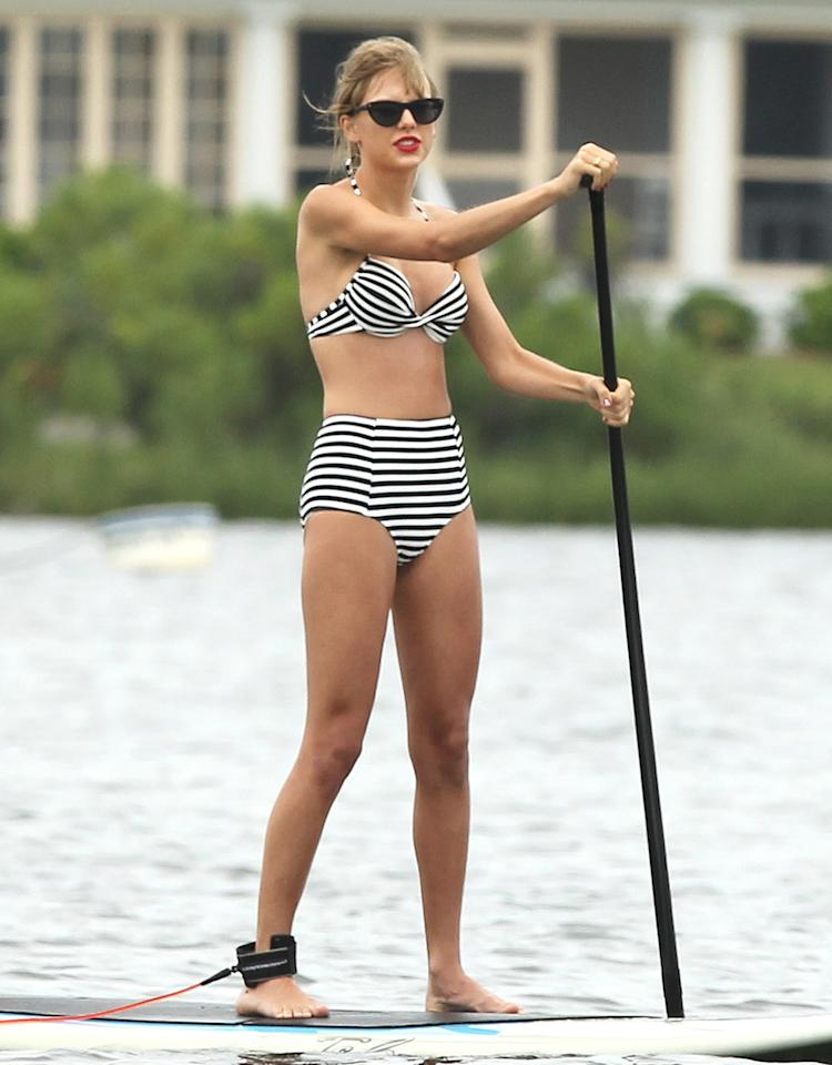 There are three things country cutie Taylor Swift needs when she hits the beach: a high-waisted bikini in black and white or red, preferably adorned with polka dots or stripes, a set of sunglasses, and some ruby red lips! The 23-year-old singer was spotted sporting her signature beach-ready attire when she took to the high seas this summer on a paddleboard in Little Narragansett Bay, Rhode Island. (7/28/2013)