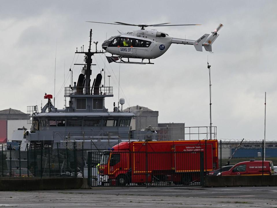 A SAMU (French Urgent Medical Aid Service) helicopter landing at Dunkerque port, northern France amid a rescue operation after a migrant boat sank on 27 October  (AFP via Getty Images)