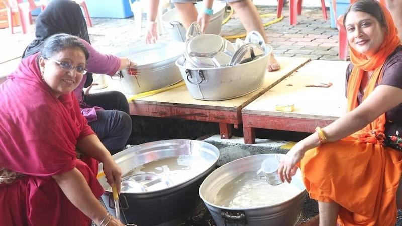 Members of the gurdwara washing kitchen utensils to be used for the Vaisakhi lunch later today. — Picture courtesy of Gurpreet Singh
