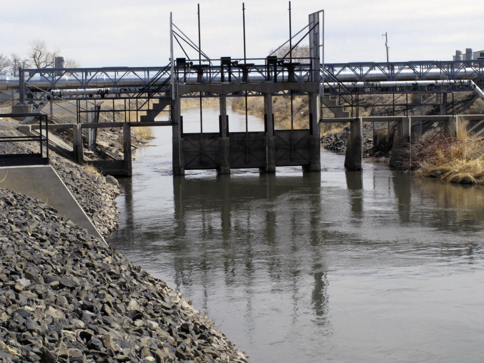 Water flows a control gate in an irrigation canal Thursday, March 18, 2021 in Fernley, Nev. The town founded a century ago by pioneers lured to the West with the promise of free land and cheap water is suing the U.S. government over plans to renovate the earthen canal that burst and flooded nearly 600 homes in Fernley in 2008. They say plans to line parts of it with concrete will eliminate leakage they've counted on for decades to replenish the groundwater aquifer they tap with domestic wells. (AP Photo/Scott Sonner)
