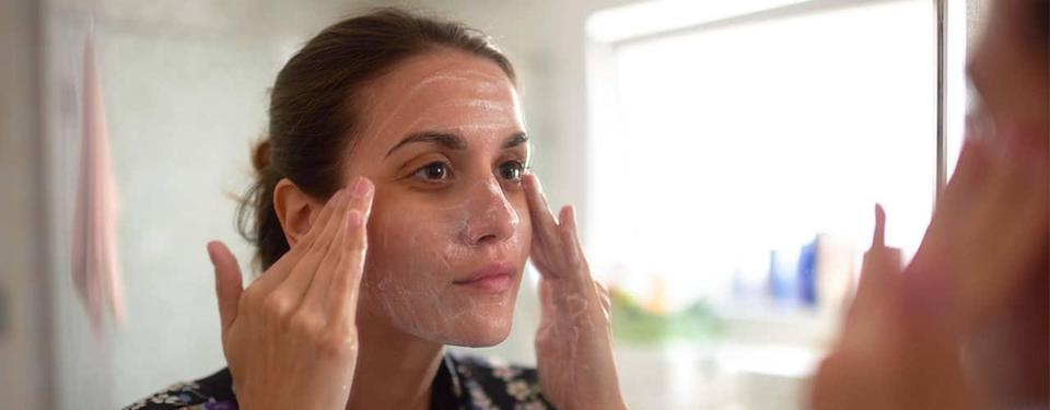 woman washing her face in the mirror