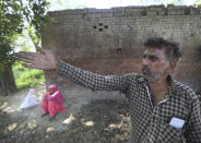 """Indian farmer Pawan Kumar, 52, a fruit and vegetable farmer who hasn't joined the ongoing farmers protests, gestures towards his field in village Samrodha, in the northern Indian state of Haryana, Friday, March 5, 2021. Thousands of demonstrating Indian farmers blocked a massive expressway on the edges of capital New Delhi on Saturday to mark the 100th day of protest against agricultural laws passed last year that they say will devastate their income. But not all farmers are against the laws. Kumar, an ardent Modi supporter, said he was ready to accept the laws. """"If they turn out to not benefit us, then we will protest again. We will jam roads, and make that protest even bigger than this. Then more common people, even workers, will join that protest. But if they turn out to be beneficial for us, we will keep them,"""" Kumar said talking about the new laws. (AP Photo/Manish Swarup)"""