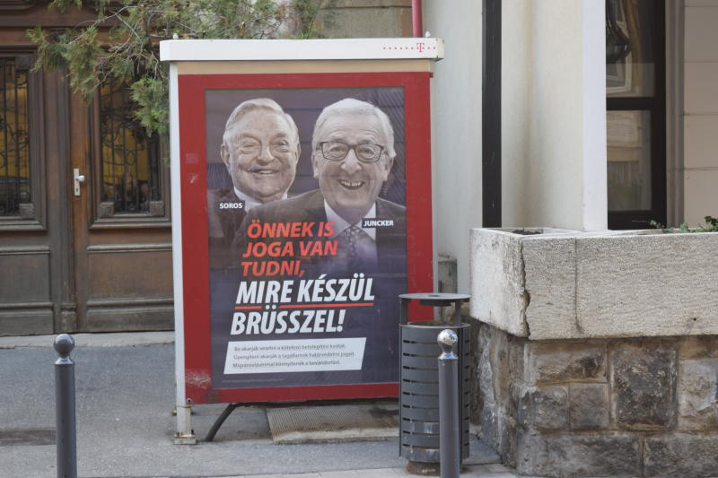 "A poster from a Hungarian government campaign showing EU Commission President Jean-Claude Juncker and Hungarian-American financier George Soros with the caption ""You, too, have a right to know what Brussels is preparing to do"" is displayed on a phone booth in Budapest, March 4, 2019. Hungarian officials said the campaign claiming that EU leaders like Juncker, backed by Soros, want to bring mass migration into Europe, would end by March 15. (AP Photo/Pablo Gorondi)"