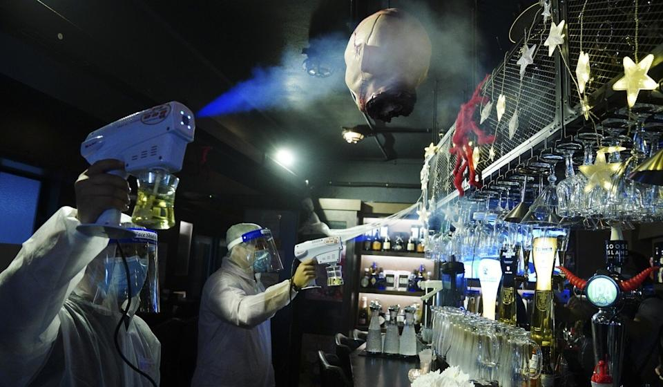 Workers spray disinfectant at a bar on Knutsford Terrace in Tsim Sha Tsui last month. Photo: Sam Tsang