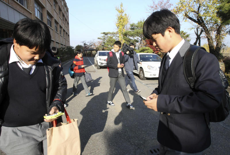 In this Friday, Nov. 9, 2012 photo, South Korean students check their smartphones after classes at Bibong Middle School in Hwaseong, South Korea. Students agreed to hand in their smartphones when they arrive at school in the morning and get them back when they leave for home after classes. Across the entire population, South Korea's government estimated 2.55 million people are addicted to smartphones, using the devices for 8 hours a day or more, in its first survey of smartphone addiction released earlier this year. (AP Photo/Ahn Young-joon)