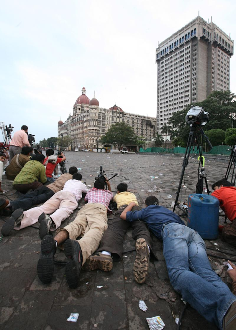 Journalists covering the attacks lie on the ground outside the Taj hotel.