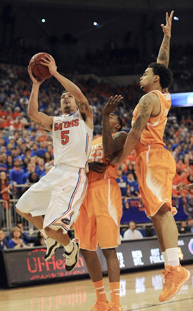 Florida guard Scottie Wilbekin (5) shoots as Tennessee guards Quinton Chievous (31) and Jordan McRae (52) defend during the first half of an NCAA college basketball game Saturday, Jan. 25, 2014 in Gainesville, Fla. (AP Photo/Phil Sandlin)