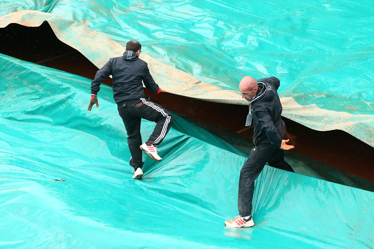 PARIS, FRANCE - MAY 30:  Court attendants pull over the covers as rain stops play during day five of the French Open at Roland Garros on May 30, 2013 in Paris, France.  (Photo by Julian Finney/Getty Images)