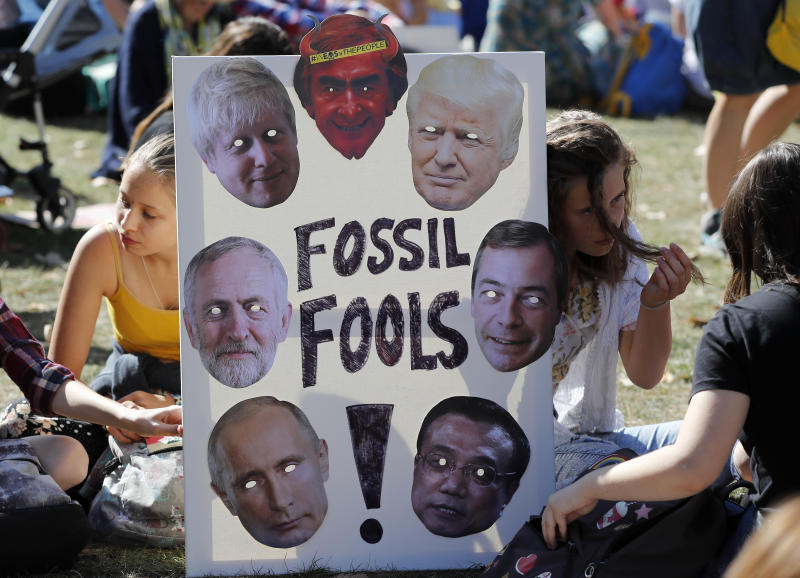 Climate protesters hold a banner bearing the images of world leaders as they demonstrate in London, Friday, Sept. 20, 2019. (Photo: Frank Augstein/AP)