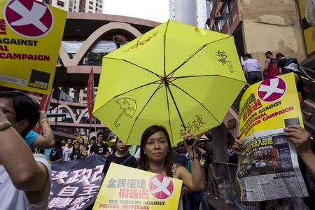 A pro-democracy protester holds a yellow umbrella, the symbol of the Occupy Central movement, during a march to demand lawmakers reject a Beijing-vetted electoral reform package for the city's first direct chief executive election in Hong Kong, China June 14, 2015. REUTERS/Tyrone Siu