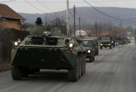 A convoy of NATO-led peacekeeping force KFOR vehicles travels on the road near the village Rudare, north of Serb-dominated part of ethnically divided town of Mitrovica, Kosovo, Thursday, Dec. 13, 2018. Kosovo's parliament on Friday is expected to approve legislation to turn existing 4,000-strong security forces into an army. (AP Photo/Darko Vojinovic)