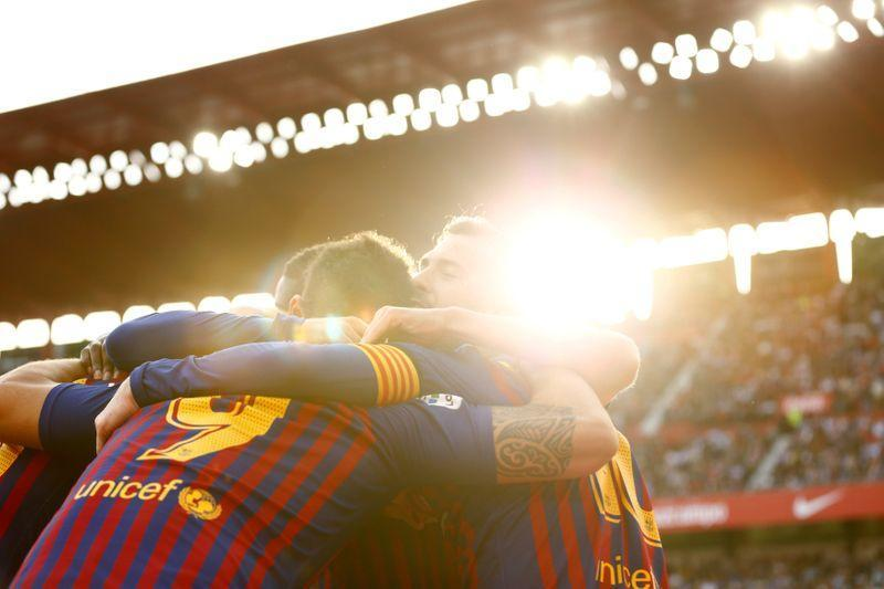 Barcelona's Lionel Messi celebrates with team mates after scoring their third goal to complete his hat-trick