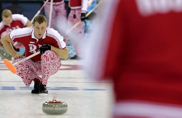 Russia's Petr Dron watches the stone during the first day of the men's curling training at the 2014 Winter Olympics, Saturday, Feb. 8, 2014, in Sochi, Russia