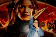 """FILE PHOTO: Student Natchacha flashes a three-finger salute inspired by the movie """"The Hunger Games"""" in front of a billboard of the film outside the Siam Paragon cinema in Bangkok"""