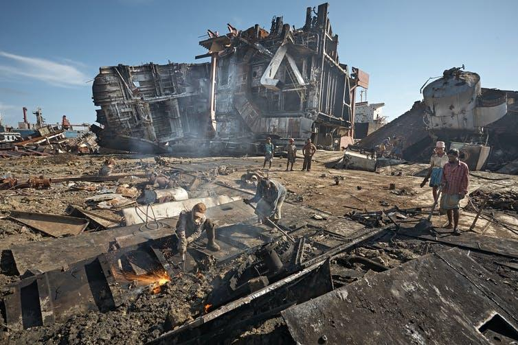 People dismantling parts of a ship, large ship on its side in the background.