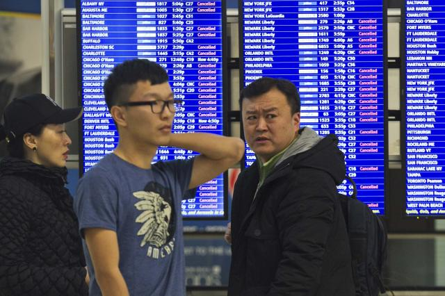 Travellers check an information monitor as weather causes flight cancellations and delays during a winter storm in Boston