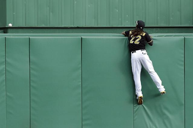Pittsburgh Pirates center fielder Andrew McCutchen hangs on to the center field wall after a two-run home run by St. Louis Cardinals' Matt Holliday in the sixth inning of Game 4 of a National League baseball division series, Monday, Oct. 7, 2013, in Pittsburgh. (AP Photo/Gene J. Puskar)